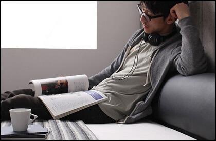 ベッドの上で読書する人写真