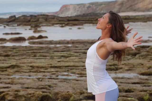 朝海辺で体操をする女性