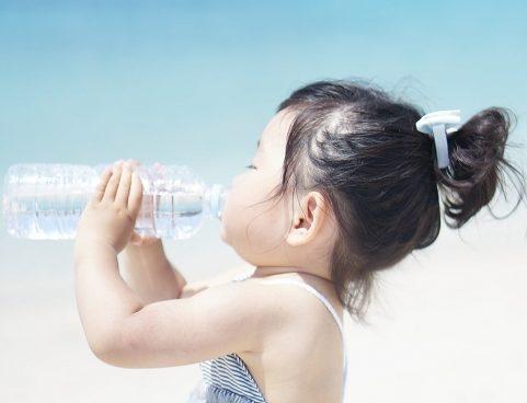 身ペットボトルの水を飲む子供