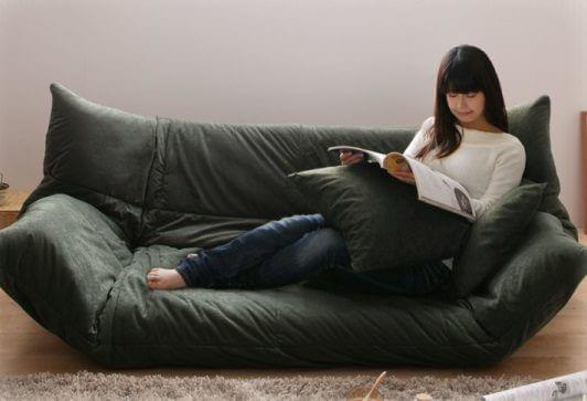 ソファに横になり雑誌をよむ女性