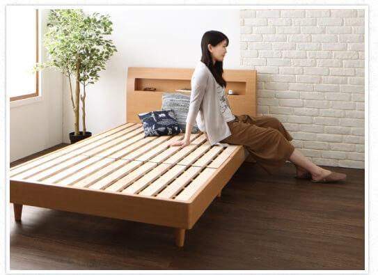すのこベッドに腰掛ける女性