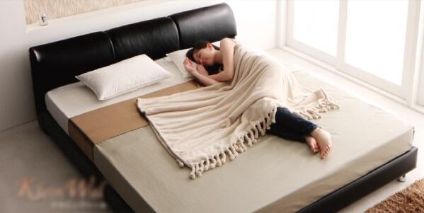 クイーンベッドでゆったり寝る女性